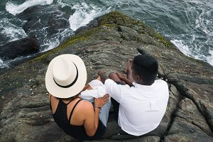 Man and woman sit on cliff together