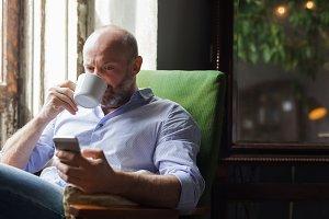 man drinks coffee reading the news
