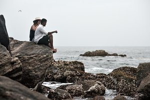 Young couple on the stone neat ocean
