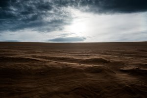 sandy dunes with dark cloudy sky
