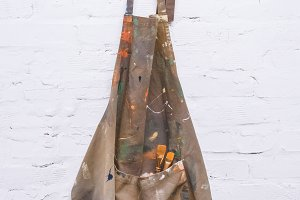 brown artist apron with paint brushe