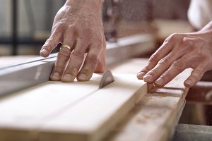 The joiner saws a piece of wood