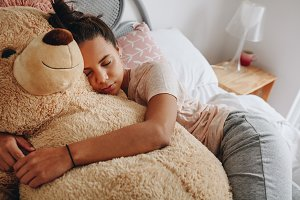 Girl sleeping on bed holding a teddy