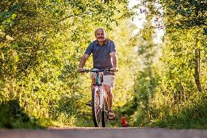 senior man riding a bike in a park