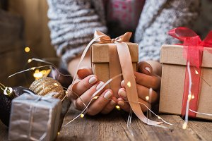 A woman holding a Christmas gift wit