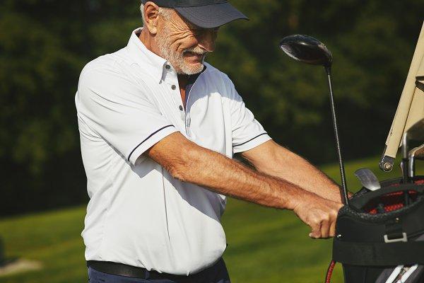 Senior man taking his club bag off…
