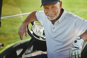 Smiling senior man sitting in a golf