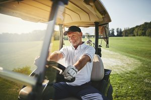 Smiling senior man driving his golf
