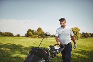 Smiling senior man pushing his golf