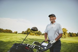 Smiling senior man pushing his clubs