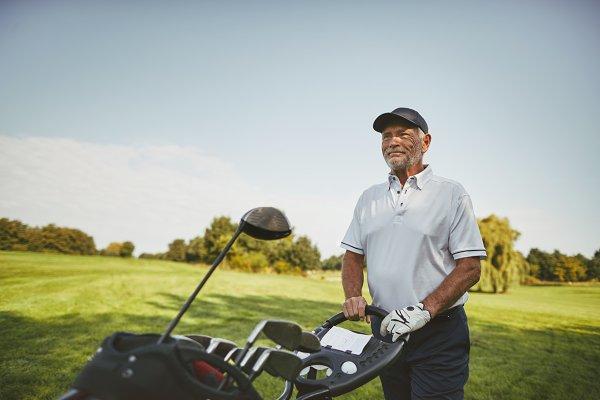 Smiling senior man pushing his club…