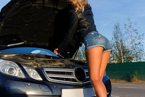 Photo of woman near broken car with