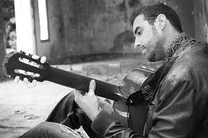 man with guitar in a ruined building