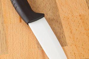 Ceramic knife on wooden cutting boar