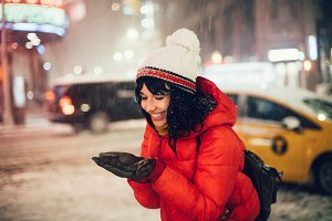 excited woman catching snowflakes