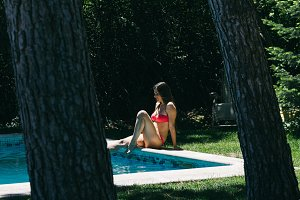 Woman sitting on the edge of a pool