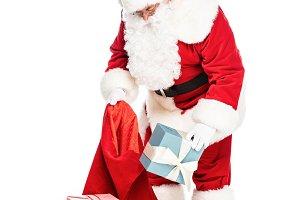 santa claus putting presents into ba