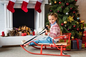 cute happy child sitting on sled and