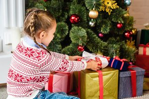 side view of cute kid opening gift b