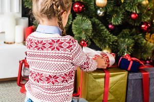 back view of cute kid opening gift b