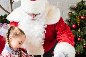 santa claus looking at little child
