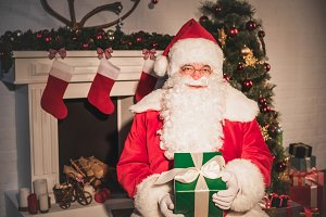 santa claus holding christmas gift a