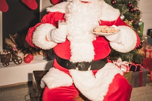 santa claus holding plate with cooki