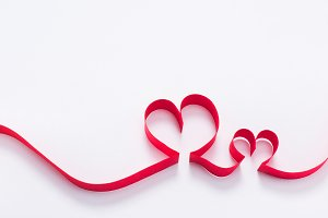 two red hearts from ribbon on white,