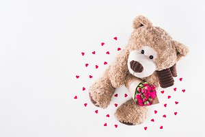 top view of teddy bear with bouquet