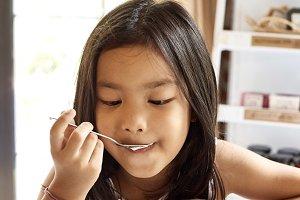 Asian girl eatting cake in cafe.