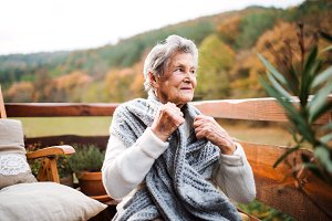 An elderly woman sitting outdoors on