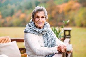An elderly woman standing outdoors