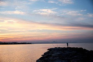 Fisherman standing on a pier at suns