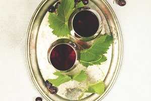 Wine and grapes over grey marble bac