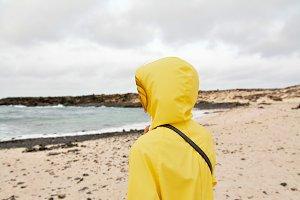 Girl on white beach in yellow jacket