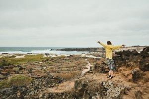 Happy girl raises hands near the sea