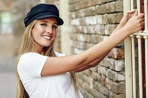 Young blonde woman wearing cap smili