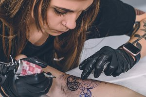 Woman tattoo artist during tattooing