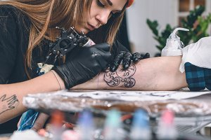 Woman creating tattoo on male arm