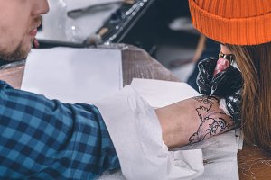 Tattoo artist in gloves working on a