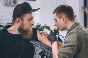 Tattoo artist and bearded man during