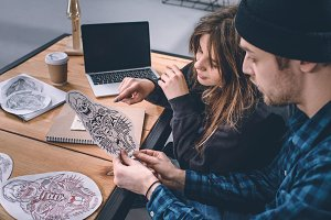 Young couple choosing tattoo design