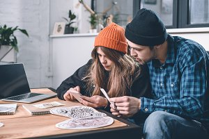 Man and woman choosing tattoo design
