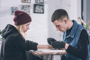Tattoo master in gloves working on a