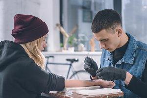 Tattoo artist in gloves working on f