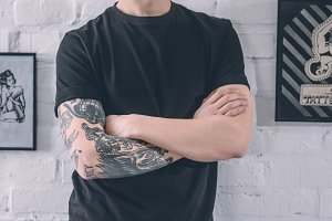 Man with tattooed arm standing by th