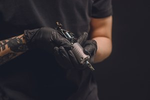 Tattoo master in gloves holding ink