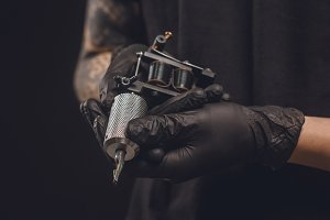 Tattoo machine in male hands isolate