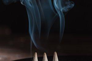 three burning incense sticks with sm