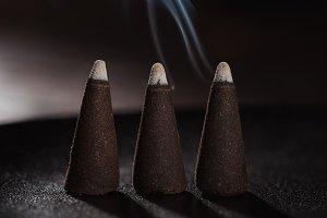 three burning incense sticks with bl